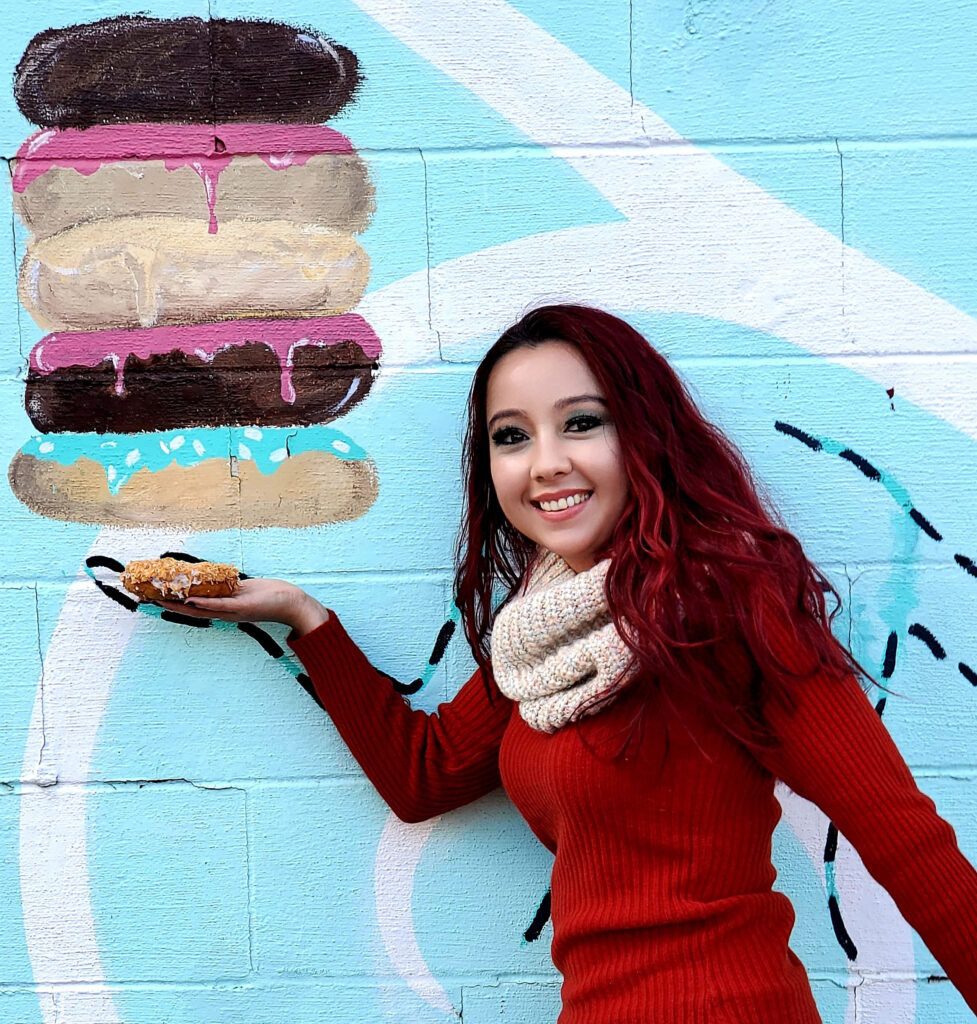 Geeves holding a donut to a donut mural