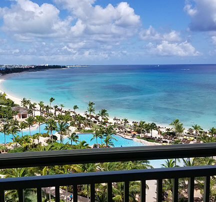 A view of the blue Caribbean ocean, hotel view, and palm trees from a balcony