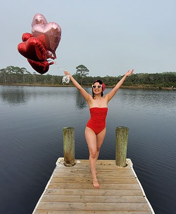 Single on Valentines Day |Geeves in red bathing triumphantly standing at a lake dock holding pink and red heart balloons