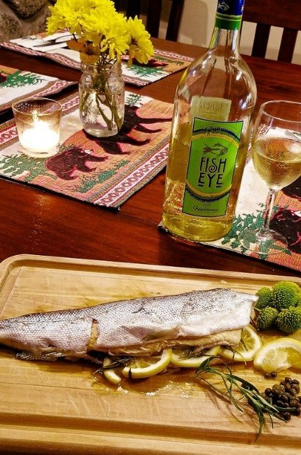 Whole salmon cooked and stuff with lemons over a cutting board and a bottle of white wine