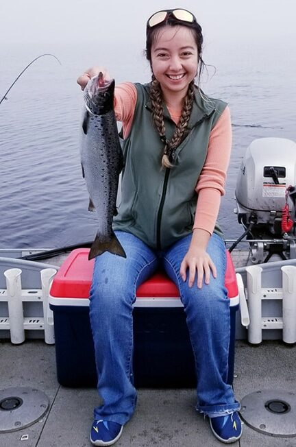 Geeves sitting on a cooler, proudly holding out the salmon fish she caught