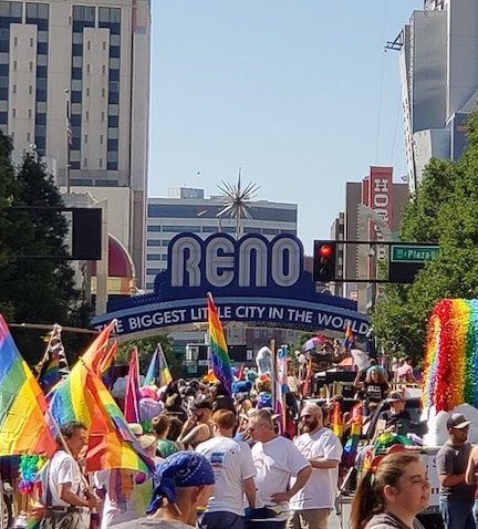 Crowd gathered in front of reno sign with rainbow flags for gay pride parade